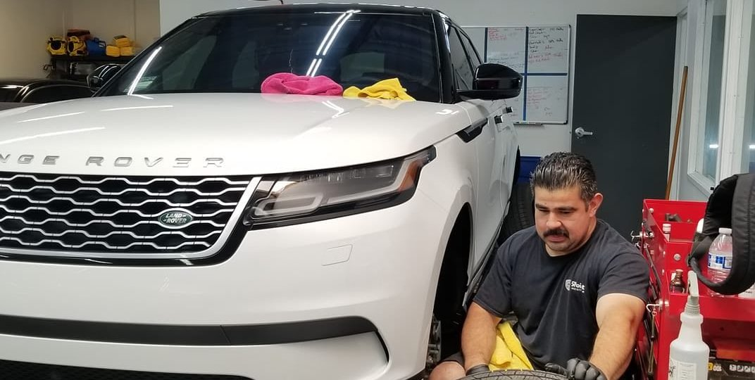 White Range Rover receiving wheel detailing and wheel protection with Ceramic Pro.