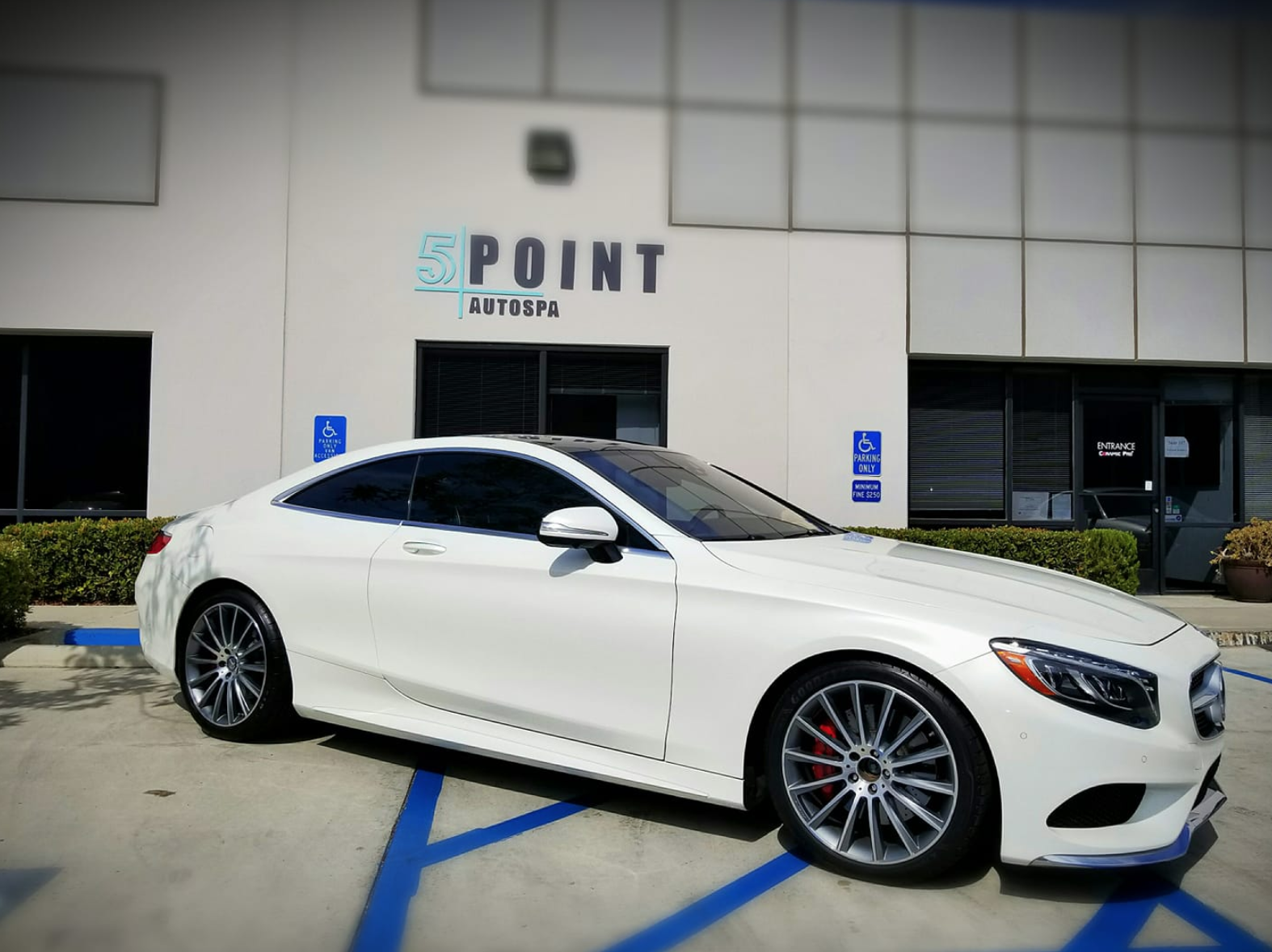 Window tinting provided by 5 Point Auto Spa on white Mercedes.
