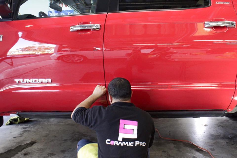 Red Toyota Tundra receiving auto paint correction by an auto detailing technician at 5 Point Auto Spa.